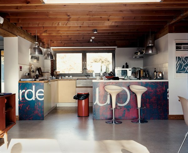 Carver and Carloss's choice of kitchen design by artist friend Neil Jolliffe reflects the couple's eclecticism and playfulness. The kitchen cabinetry draws from the soft pastel shades often seen in English coastal towns. The lighting fixtures are Giant Pendants from Original BTC.