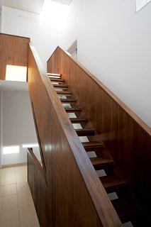 Despite its dark and boxy exterior, the house's interior is bright, naturally lit, and spacious. Adjaye, a master of the well-placed window, is in top form here. The staircase ascends toward sunlight.