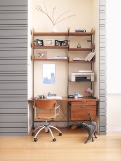 The office cubby, outfitted with a diminutive window, is furnished with Atlas shelving.