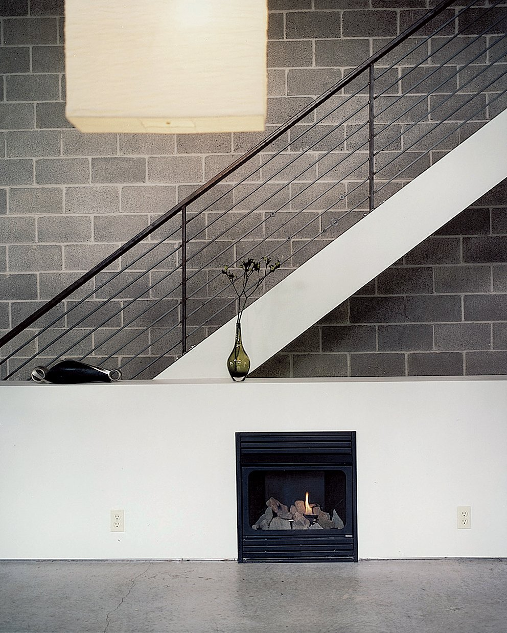 Still life with IKEA lampshade and ventless fireplace. The unfinished, black, welded-steel railing borders steps made of framing lumber, which emit a friendly, old-fashioned creak as Walz treads up and down.  190+ Best Modern Staircase Ideas from Pittsburgh Steeler