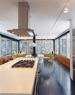 Fully enclosed by glass, Hiller's kitchen and living room give the feeling of being in a tree house.