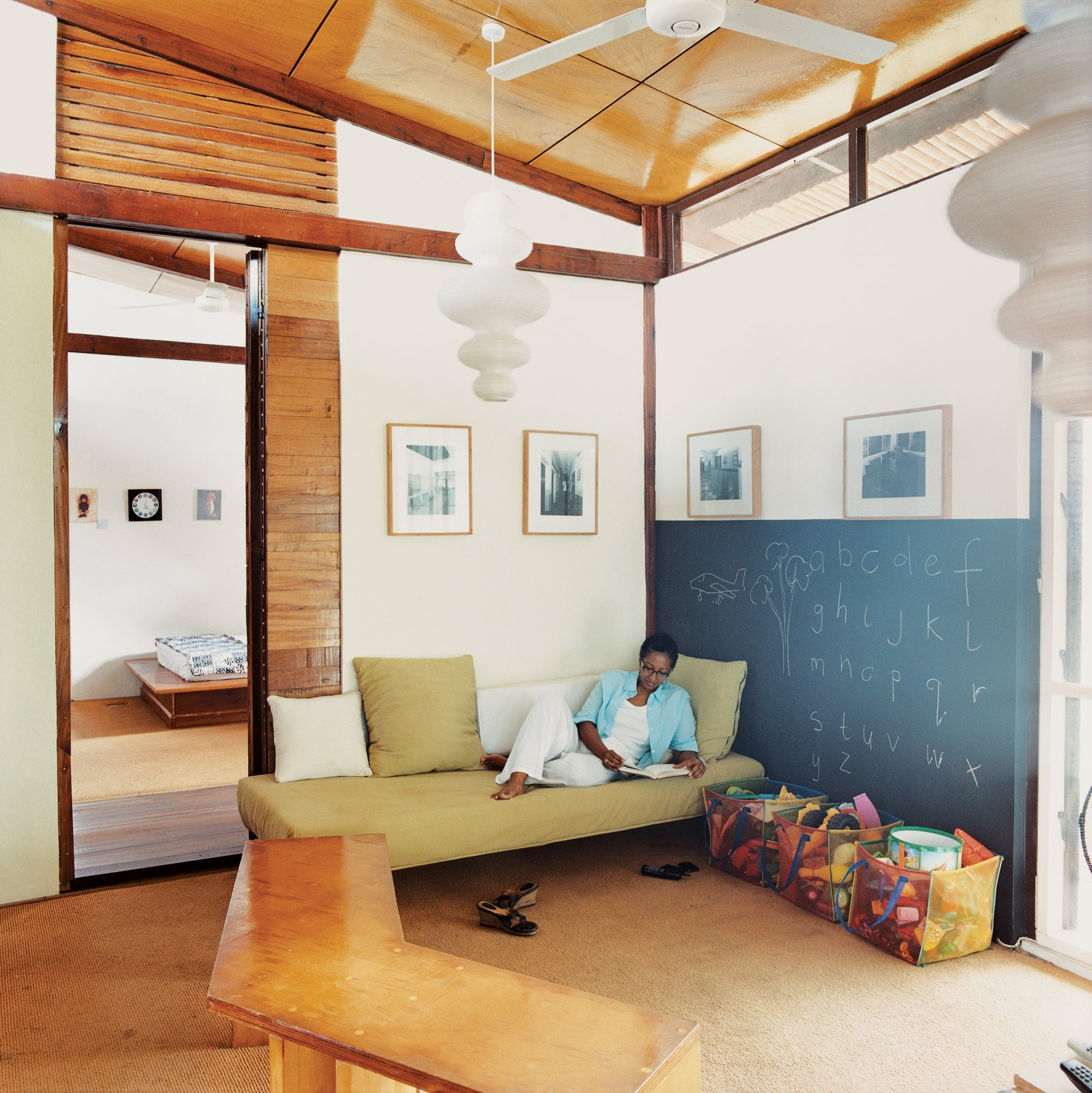 Sara Asafu-Adjaye rests on a couch in the TV room. The IKEA light fixture and other imports give the house its blend of Western and African, mass-produced and handmade.  Photo 4 of 9 in An Inno-native Approach