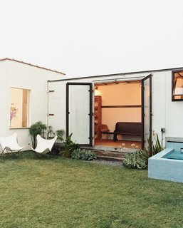 Expansive steel-and-glass doors open from the trailer to Siegal's back yard.