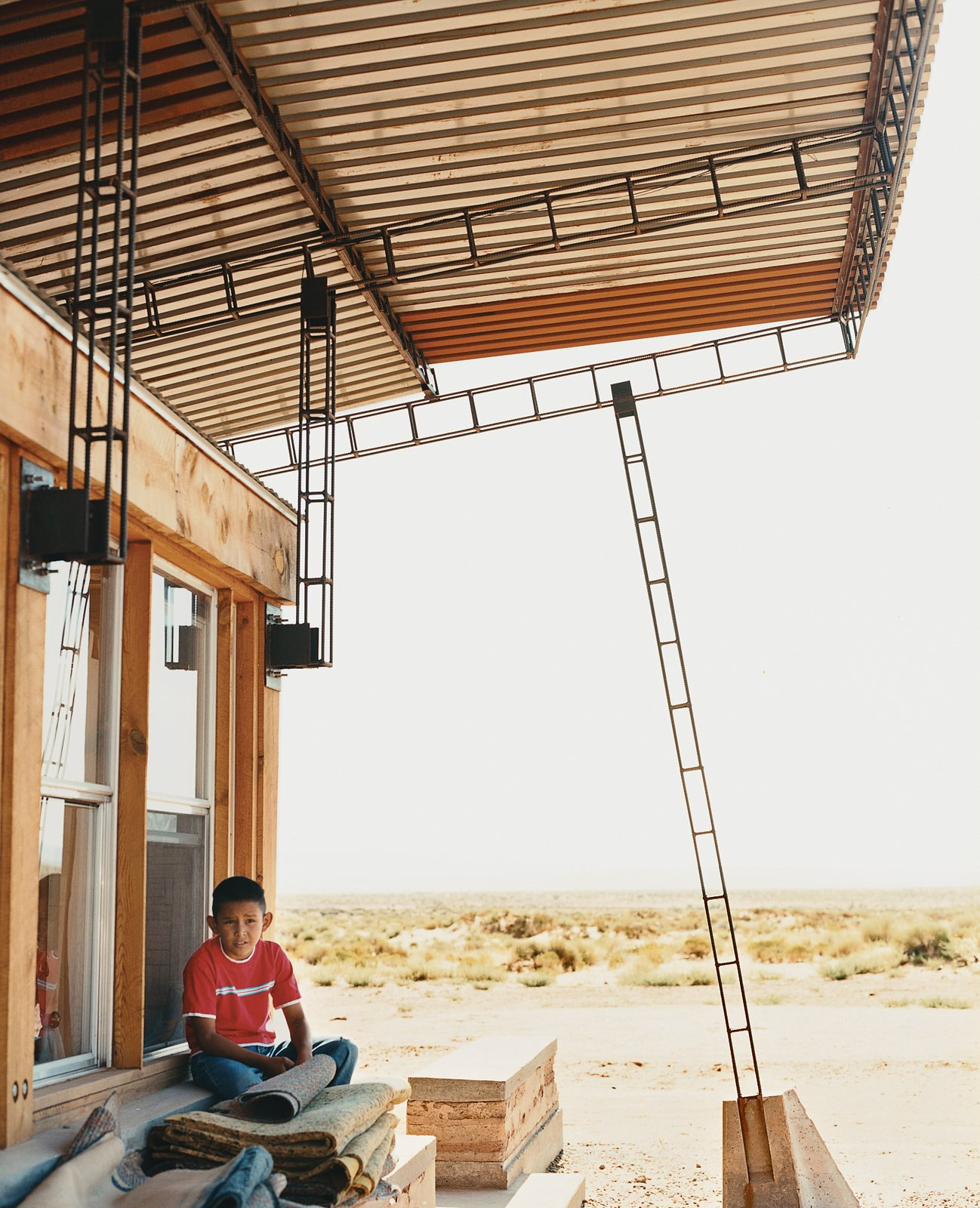 Nicholas sits in the shade of the roof; students cut and hand-welded thousands of reclaimed rebar pieces into a complex grid that would support four bi-level   corrugated-steel roof panels.  Photo 3 of 8 in No Grid in Sight