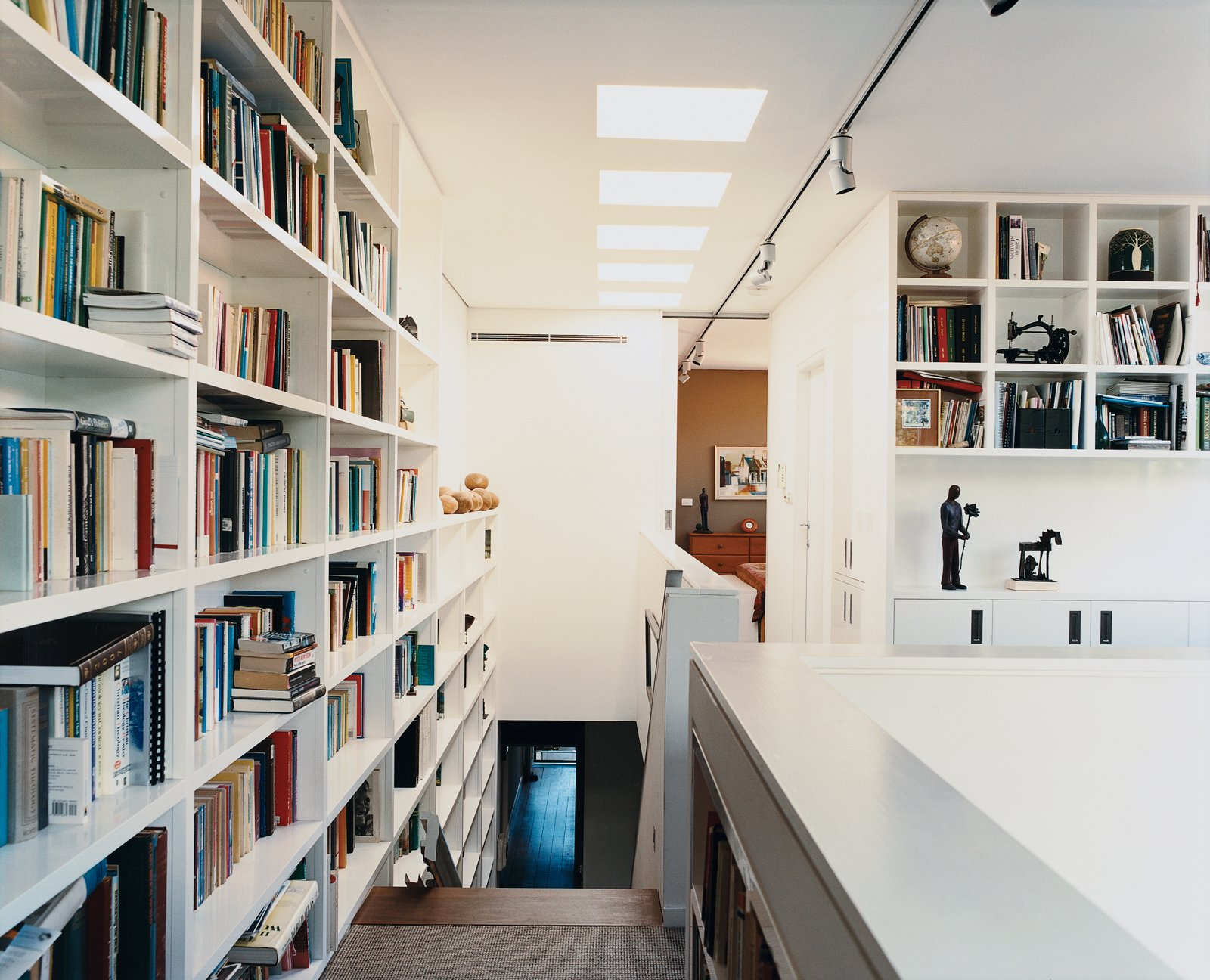 Storage Room and Shelves Storage Type A wall of books travels the height of the stairs leading to Ann Wansbrough's office, which rests comfortably on the top floor despite her limited mobility.  13+ Clever Bookcase Solutions by Erika Heet from The First Wave