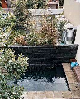The lush backyard garden, with therapy pool in the foreground, hosts the green wall, which reduces the house's drain on city water by 75 percent. Hidden behind the stone feature wall are three 800-gallon rainwater tanks that store whatever water falls from the skies.