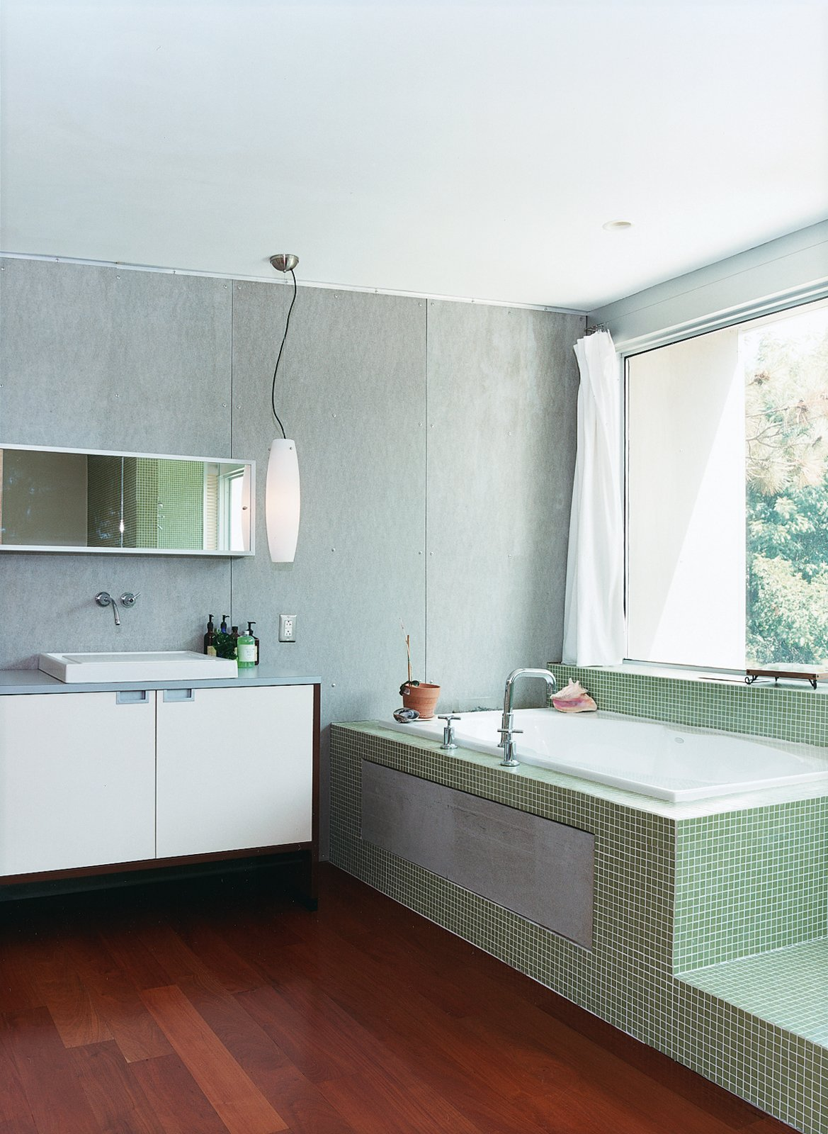 Bath Room, Medium Hardwood Floor, Drop In Sink, Pendant Lighting, and Drop In Tub The master bathroom, outfitted with Bisazza tiling, has a view of the backyard from the tub.  Photo 4 of 11 in Tile Talk: 5 Most Popular Shapes and How to Use Them from Home Schooled