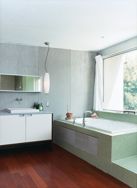 The master bathroom, outfitted with Bisazza tiling, has a view of the backyard from the tub.