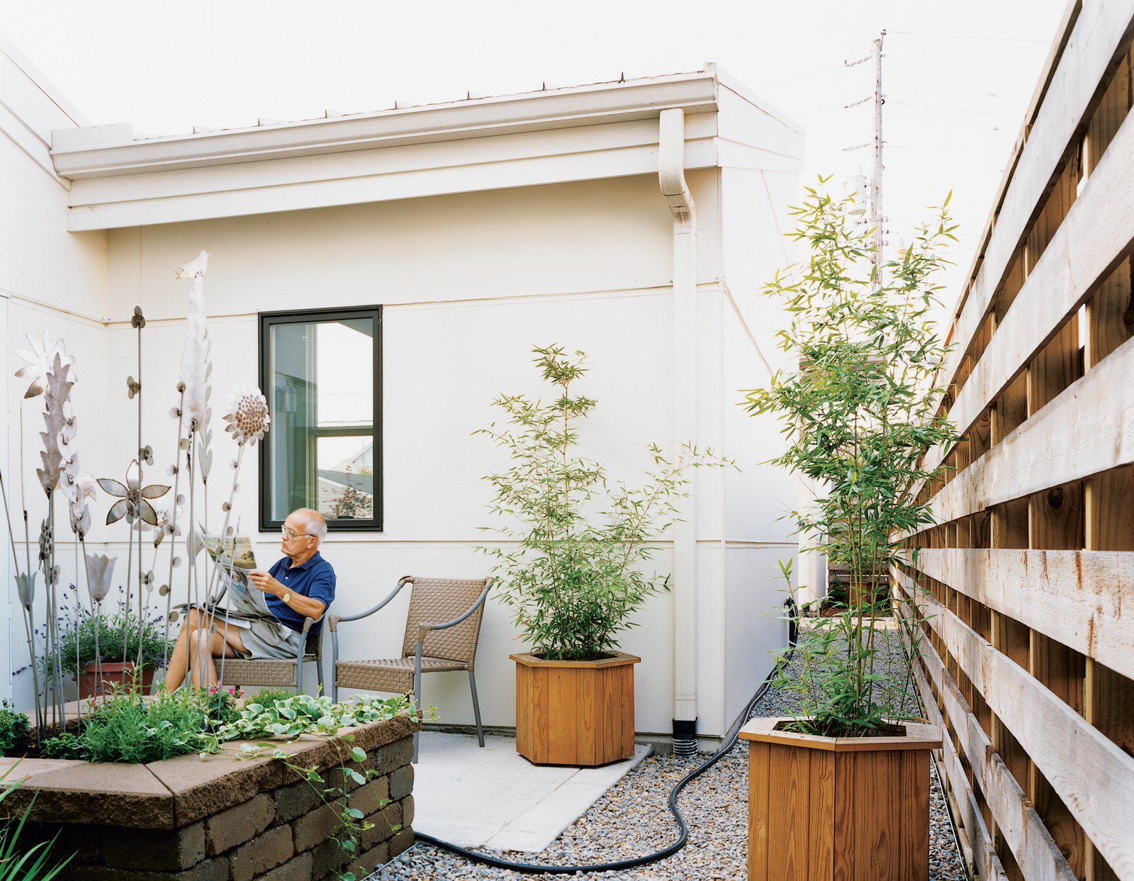 "The Brachers spend large amounts of time lounging in their courtyard spaces, as Peter demonstrates. ""Whatever room you're in on the first floor, you're looking at some type of garden. That was the whole idea of the project,"" the architect explains.  Photo 4 of 4 in Suburban Flight"
