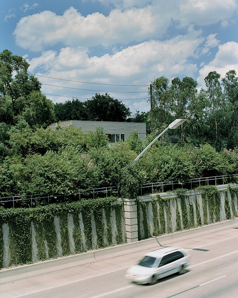The house is sheltered from the speeding traffic on Highway 59 by a fortress of trees.  Photo 1 of 12 in Houston, TX