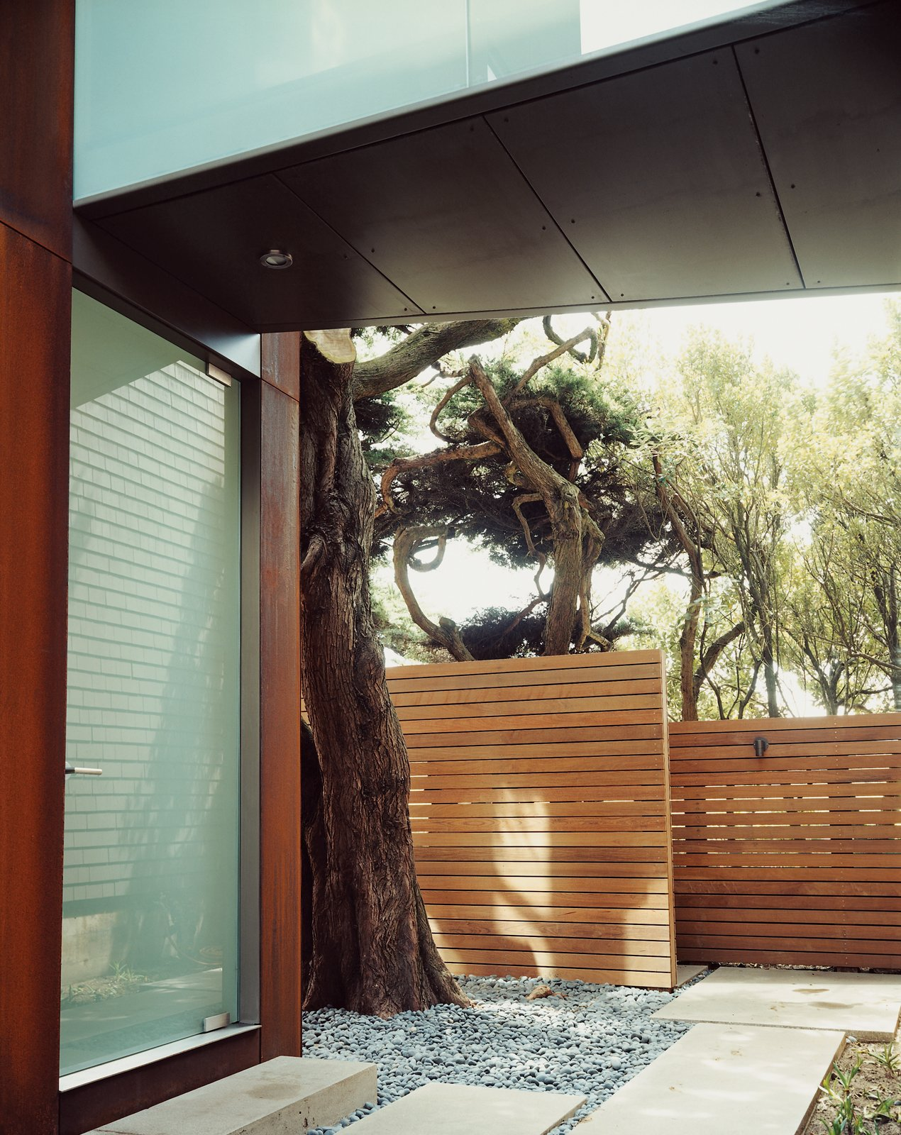 The cypresses beyond the ipe fence afford the family privacy.  30+ Best Modern Fences by William Lamb from This Surfer's Beach House is More Than It Seems