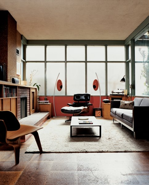 The bank of translucent glass windows diffuses light evenly in the living room and contributes to the sensation that you have left the world behind. Eames chairs for Herman Miller are accompanied by Italian manufacturer U-vola's unique speakers from Elite Audio Systems.