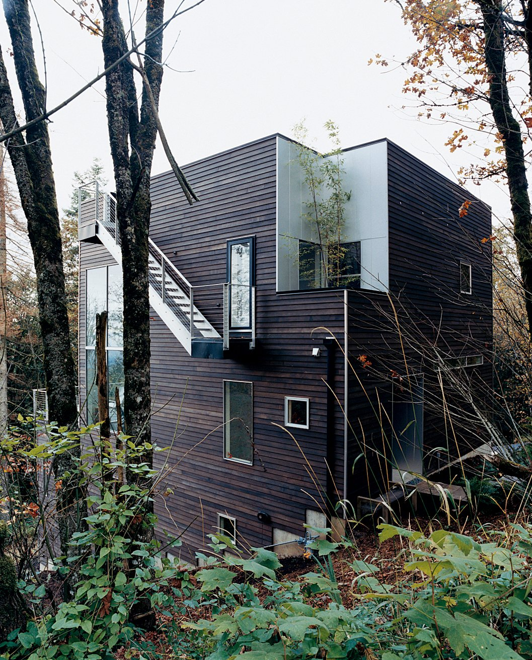 Exterior, Wood Siding Material, Cabin Building Type, House Building Type, and Flat RoofLine The wooded site allowed for  soaring, curtainless windows that the couple couldn't have enjoyed downtown.  Photo 2 of 8 in Aloft in the Forest