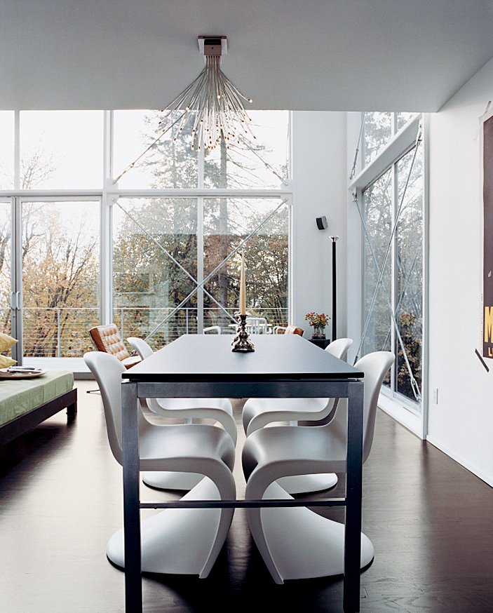 Dining Room, Table, Chair, Pendant Lighting, and Ceiling Lighting The house's open spaces are minimally furnished with modern classics like Verner Panton chairs in the dining area.  Photo 7 of 8 in Aloft in the Forest