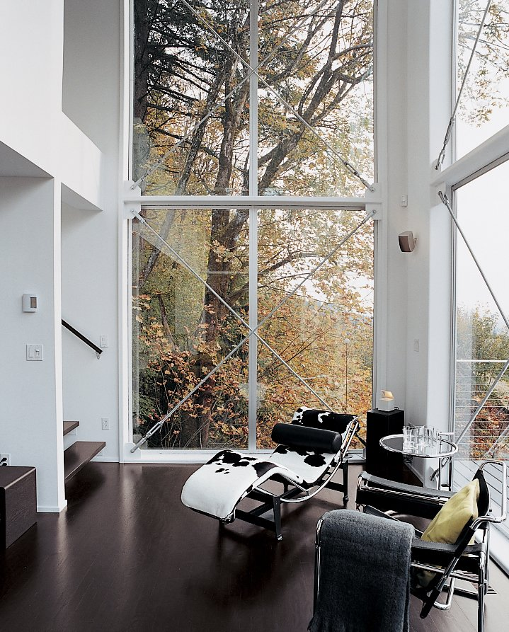 Living Room, Recliner, and Dark Hardwood Floor A Corbusier chaise and Eileen Gray end table fill out the corner of the couple's high-ceilinged living area, which helps create the desired loftlike feel of the home.  Photo 8 of 8 in Aloft in the Forest
