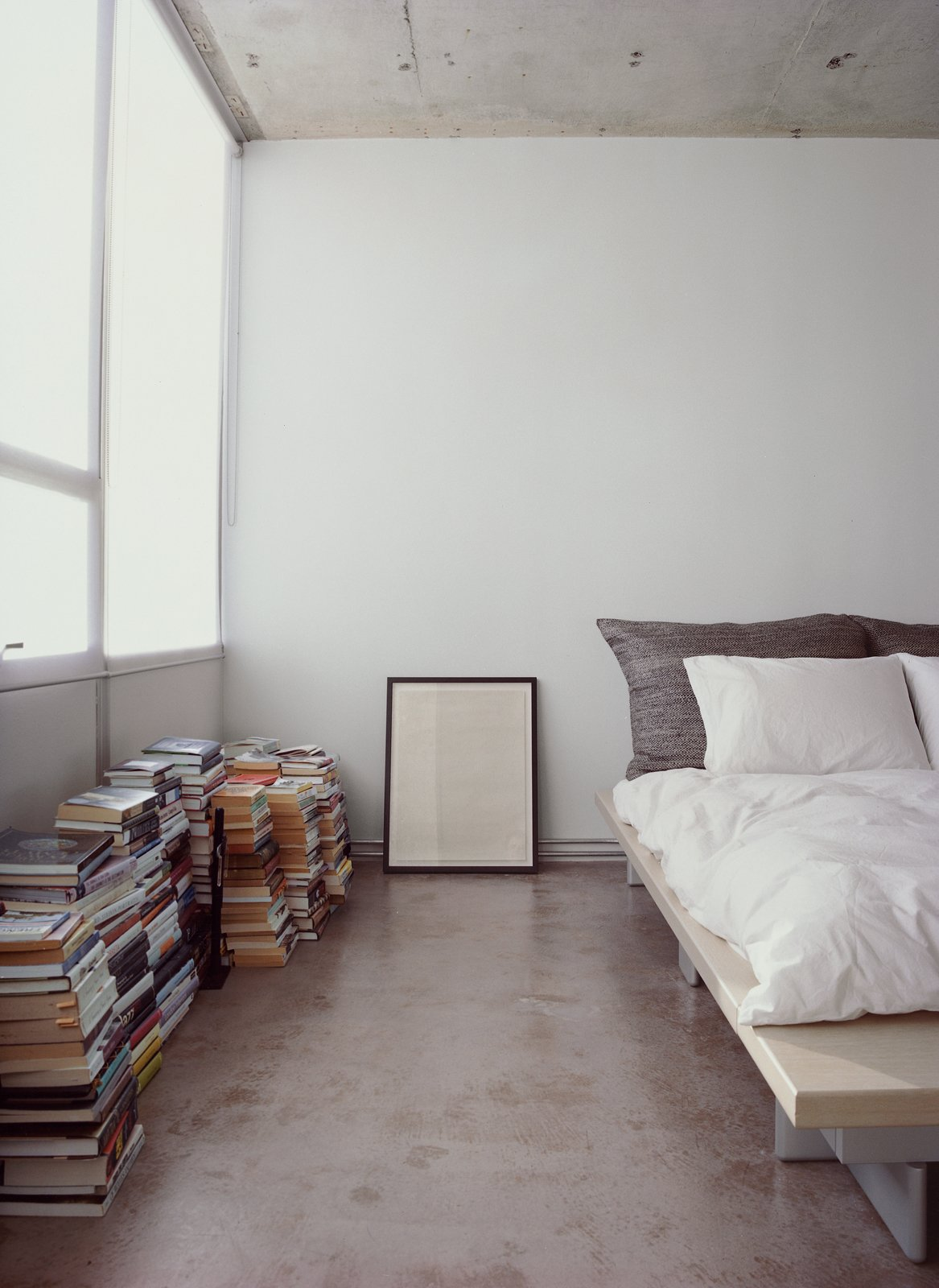 Bedroom, Bed, and Concrete Floor Who needs shelves when there's plenty of floor space? Stacks of books and a framed print sit alongside a Peter Maly Ligne Roset bed, reupholstered in stiff linen.  Photo 8 of 11 in Stripped Ease