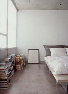Who needs shelves when there's plenty of floor space? Stacks of books and a framed print sit alongside a Peter Maly Ligne Roset bed, reupholstered in stiff linen.