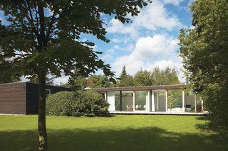The main living space is constructed of immense I-profiles, allowing for a full wall of glass with four large sliding doors that open to the backyard.