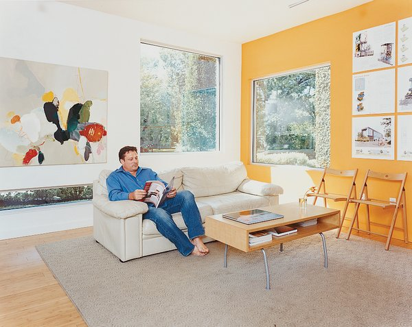 Baird relaxes in the bright living room, which is decorated spartanly with the architect's own artwork, a couch, and a coffee table by IKEA.