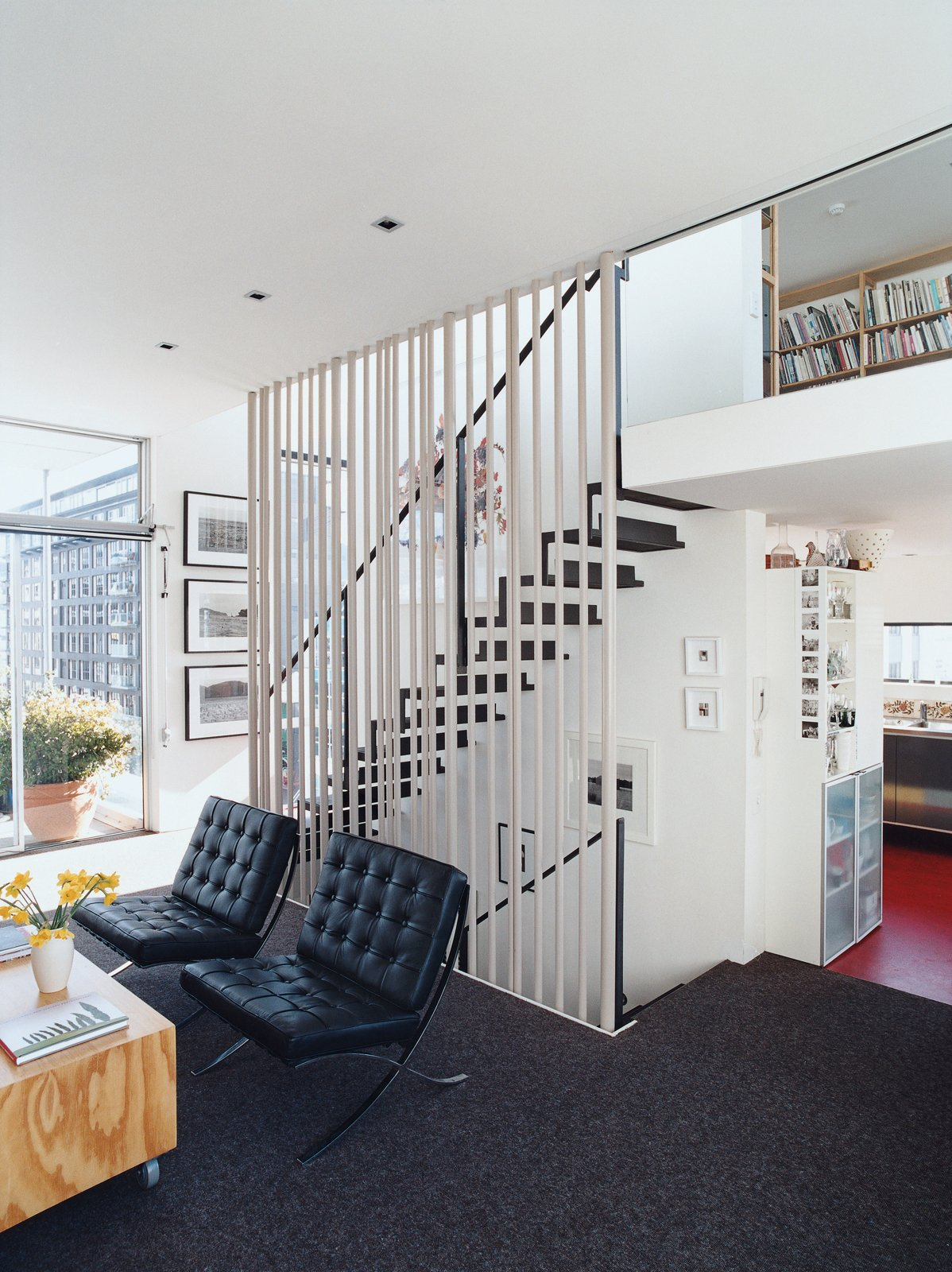 Living Room and Chair A floating steel staircase ties the living area and loft together. Variegated steel tubes provide graphic punch while maintaining the apartment's airy and open feeling.  Clever Loft Spaces for Small Places by Diana Budds