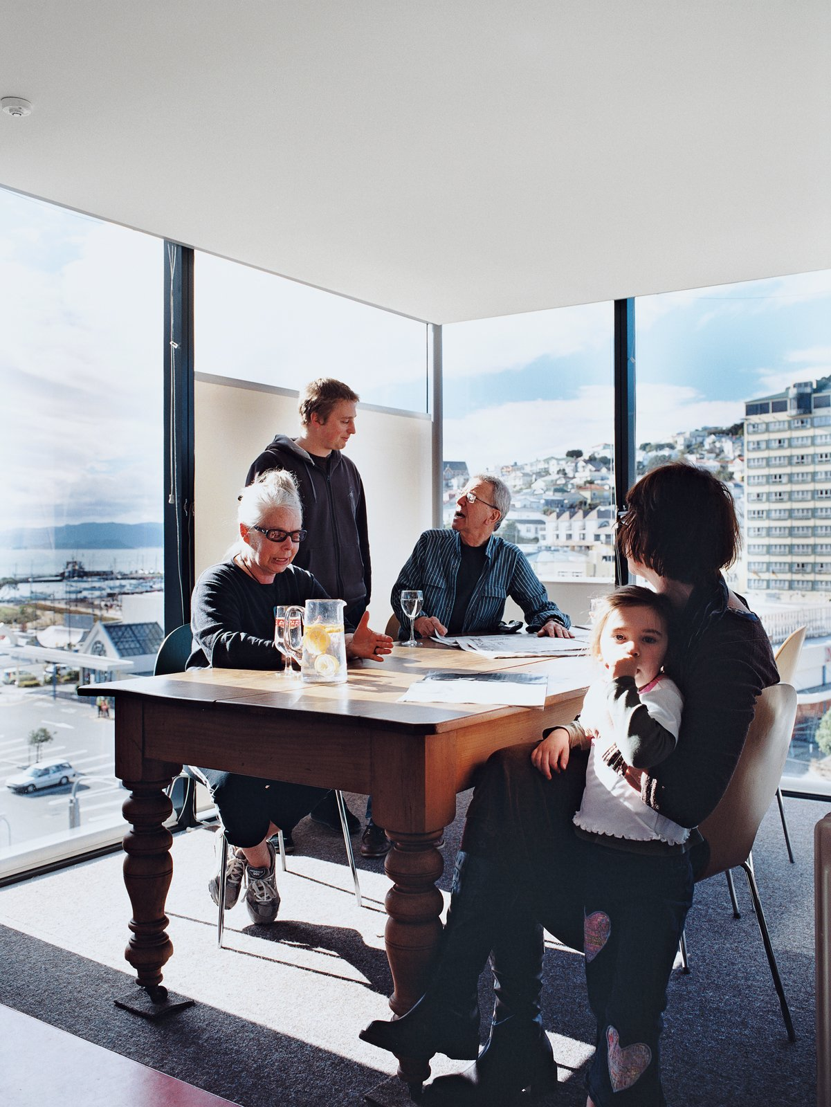 Jan Bieringa (seated, left) hangs out with her son, Kris Bieringa (standing), Tony Hiles, Judith Fyfe, and Fyfe's granddaughter, Phoebe Pottinger. Surrounded on three sides by glass walls, the dining room is the perfect spot to soak up the stunning views of Wellington Harbor and the hilly eastern suburbs.  Photo 5 of 10 in Rising Above It All