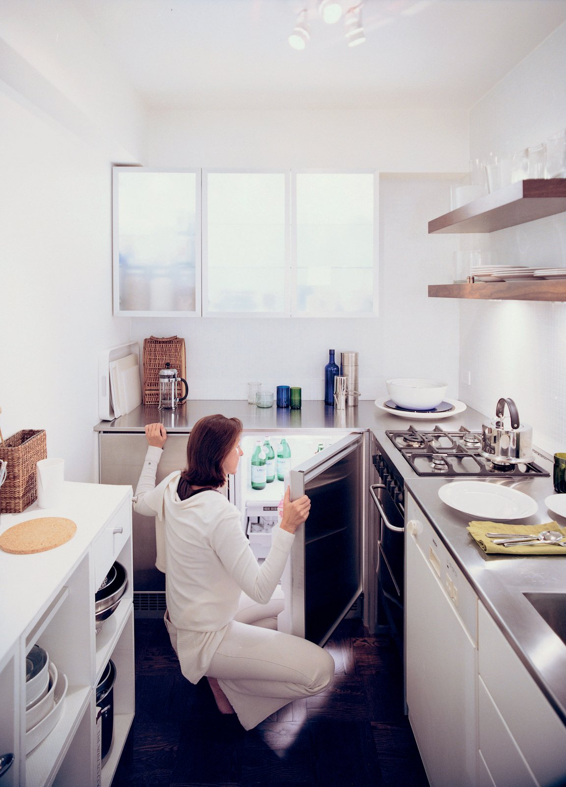 Goolrick reoriented the kitchen and chose sleek stainless steel countertops and bright white walls and cupboards to create the illusion of space.  Solutions For Tiny Kitchens by Aileen Kwun from Urban Vessel