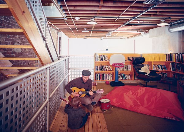 Kids Room, Playroom Room Type, Medium Hardwood Floor, and Shelves In the family room, Lucien gets an early start on his music career with his father's help. The space, technically the third floor of the structure, overlooks the central living area below.  Photo 5 of 5 in A House Grows in Brooklyn