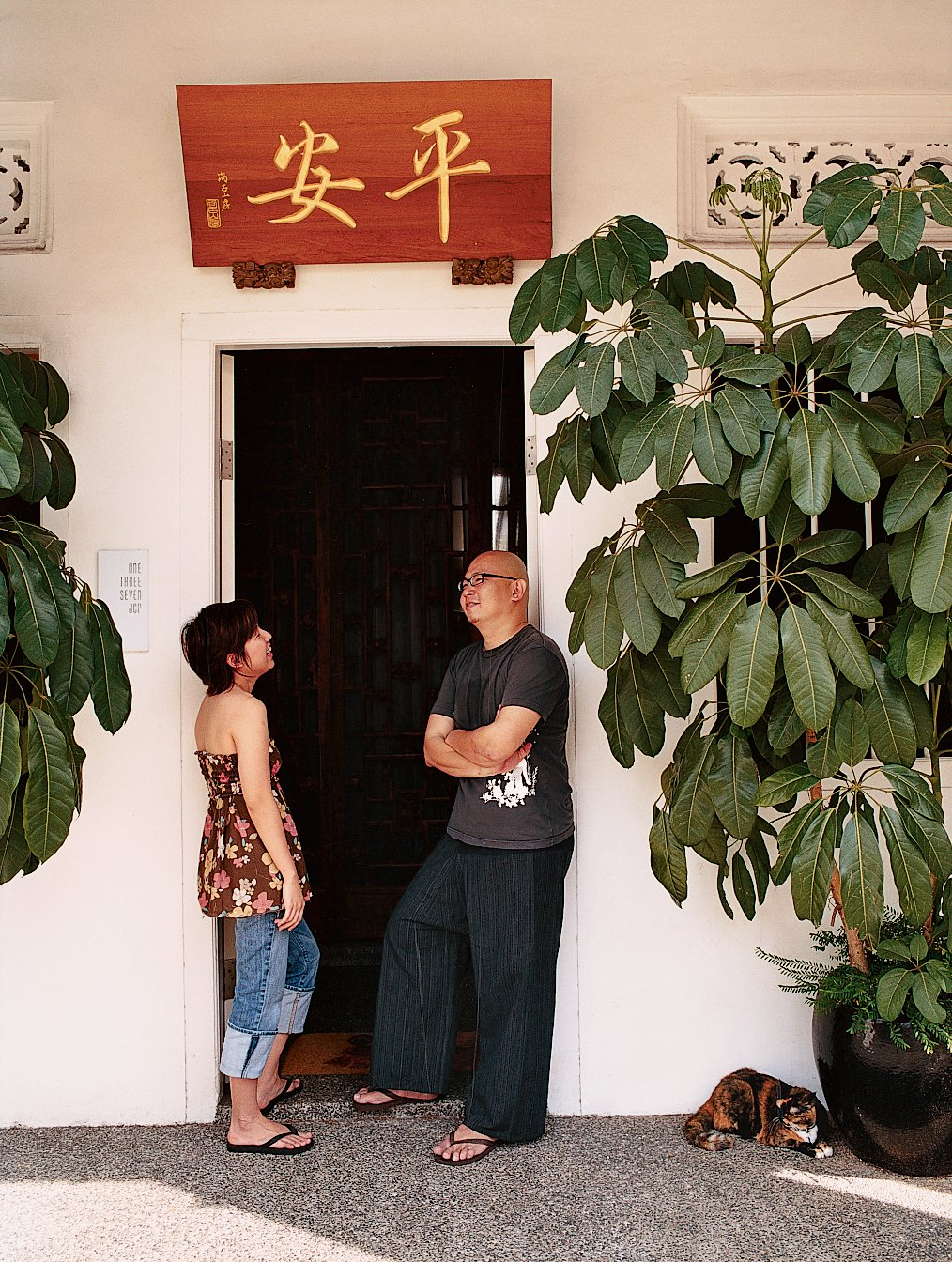 """Doors, Exterior, and Swing Door Type Ian and Yeo's house was uninhabitable when they purchased it in 2002. Three months later, the roof caved in. The translation of the sign above the door of the couple's renovated house (right) is """"peace.""""  Photo 1 of 9 in Straight and Narrow"""