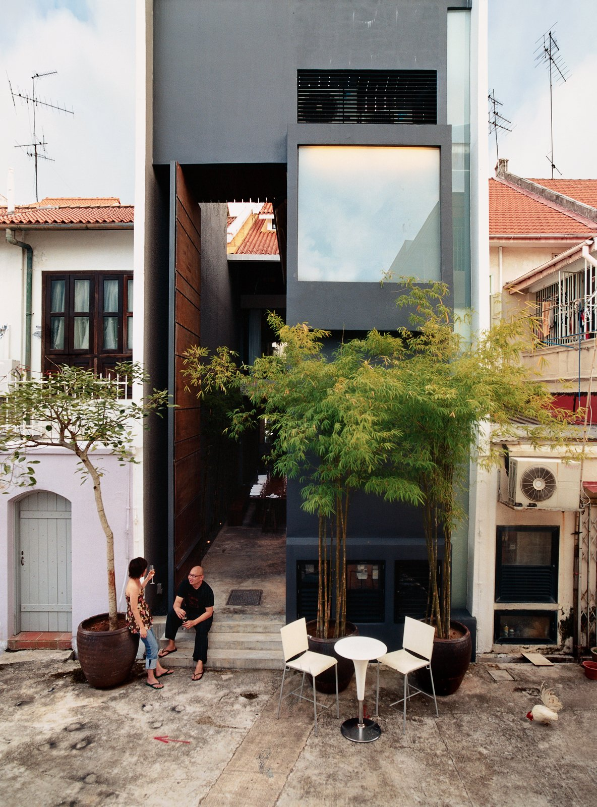 "Exterior, Metal Siding Material, and House Building Type Yang Yeo and his girlfriend Ching Ian relax on the back stoop of their renovated and radically updated Singapore shophouse—an archetypal building type in this busy port city. ""Shophouses brought back memories of our childhood,"" says Yeo.  Best Photos from Straight and Narrow"