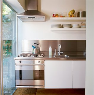 """You can stand in one space and reach everything,"" explains Colin of the precise kitchen layout with its custom-made stainless steel countertop, cantilevered cupboards, and integrated cooktop and oven. The cupboards' shallow shelves were specially made to take up minimal space and to fit Muji storage jars."