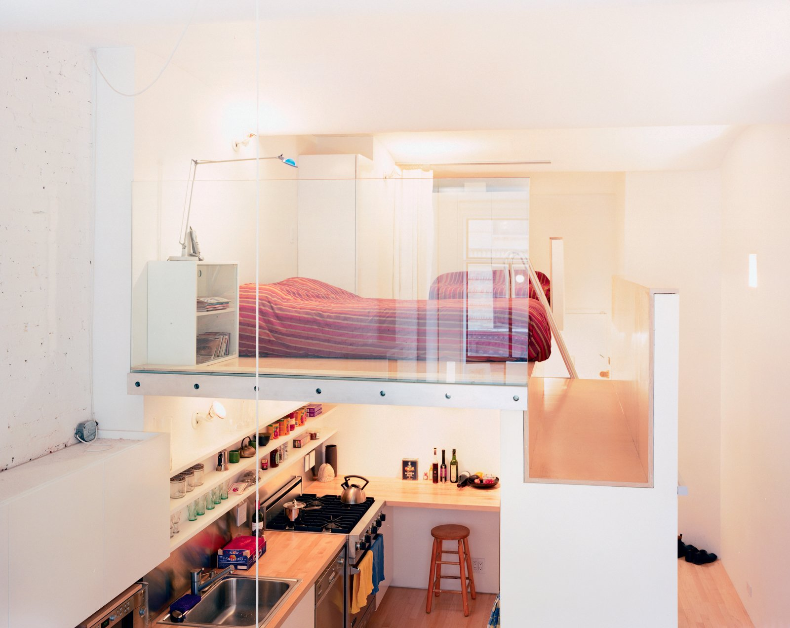 """The volume that both incorporates the single closet (accessible from the hallway) and the refrigerator (which opens into the kitchen) and serves as the bedroom floor is, says Kyu Sung Woo, """"where everything comes together.""""  Photo 2 of 7 in Big City, Little Loft"""