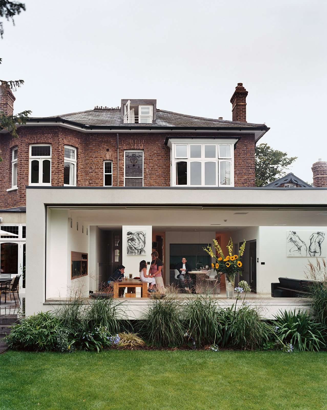 """Outdoor, Grass, and Back Yard Architect Gregory Phillips connected the original house to a new modern extension that doesn't interfere with the surrounding houses. """"I try to be true to the location,""""he explains, """"so it doesn't seem like some spaceship has landed.""""  Best Photos from Victorian Secrets"""