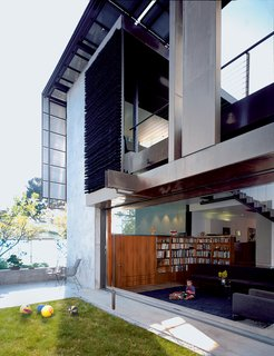 """In Scarpa and Brook' own house, they've mounted luminous solar panels in a rusted-steel-beam grid to form a modernist canopy that frames the façade. This imaginative """"solar umbrella"""" hides the household power plant in plain sight, part of an artful composition that includes a hanging screen tied with bristles of industrial brooms."""