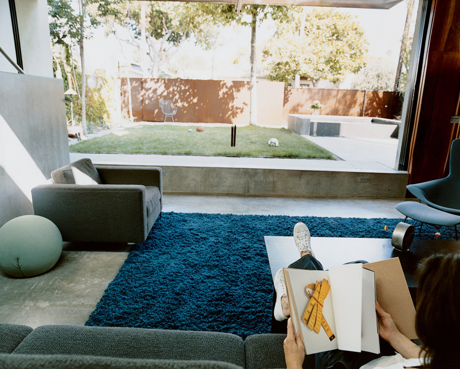 The living room flows effortlessly out to the courtyard. This unity is underscored by the living room's blue shag rug from the Shag Rug Company.  Photo 1 of 8 in Solar Inspiration