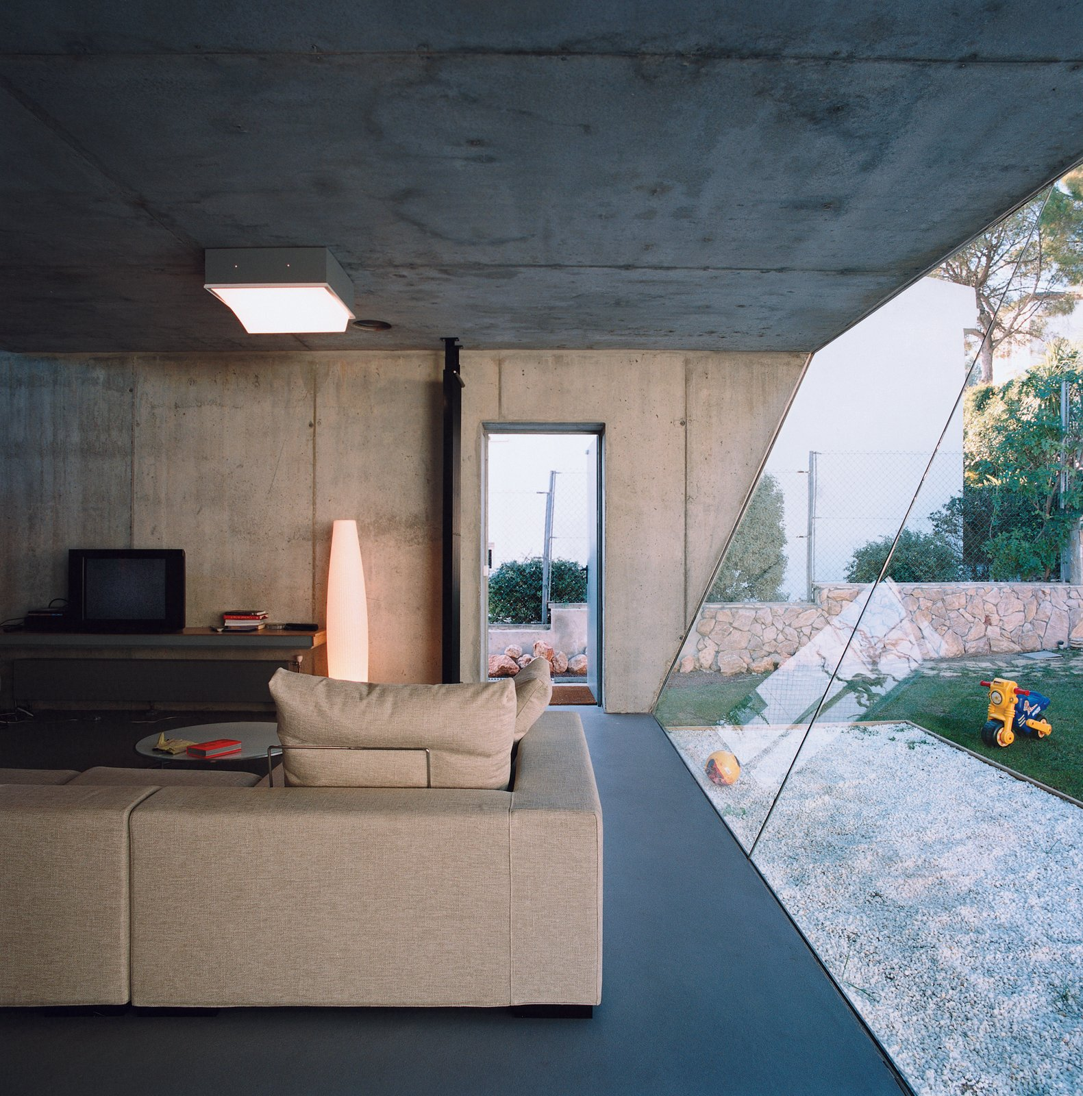 Living Room, Sofa, Ceiling Lighting, and Concrete Floor On the living room ceiling a Sivra fixture by iGuzzini modulates its output based on the amount of available daylight. The sofa is Wall by Piero Lissoni for Living Divani.  Photos from Suburban House of the Future by Cloud9