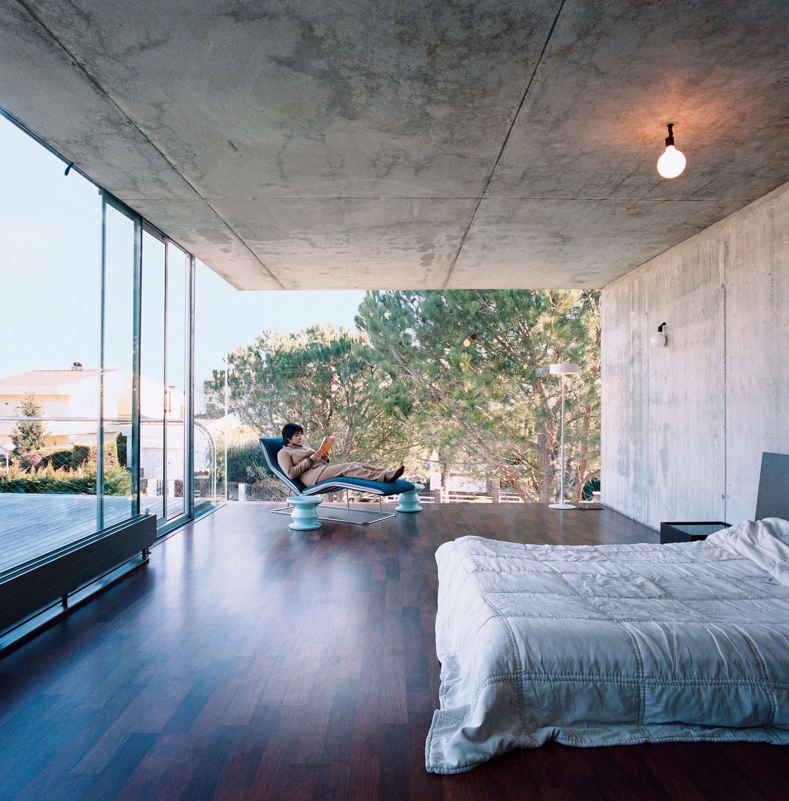 Bedroom, Bed, Chair, Ceiling Lighting, and Dark Hardwood Floor Giovanna de Uzin Fontecha relaxes in the master bedroom on a Leaf chaise by Claesson-Koivisto-Rune for Living Divani.  Striking Exposed Concrete Interiors by William Harrison from Suburban House of the Future by Cloud9