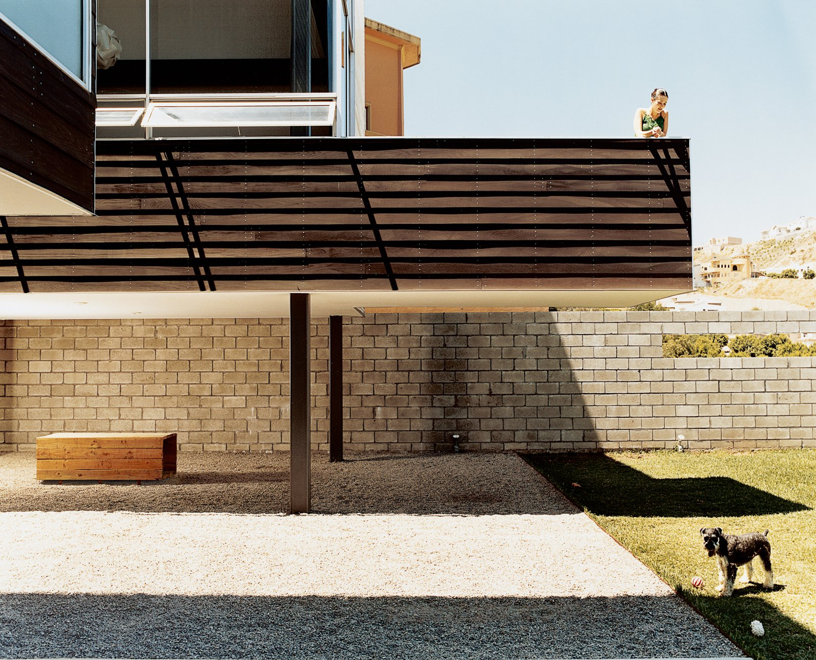 """Outdoor, Grass, Large Patio, Porch, Deck, and Stone Patio, Porch, Deck Paola Gracia keeps an eye on Kata, one of the couple's schnauzers, from the second- story balcony. In the shade below the balcony is the dogs' house, meant to mimic the Gracias', that architect Jorge Gracia built from leftover building materials.  Search """"madrid couple remake apartment one their childhood buildings"""" from A Party House in Hacienda Agua Caliente"""