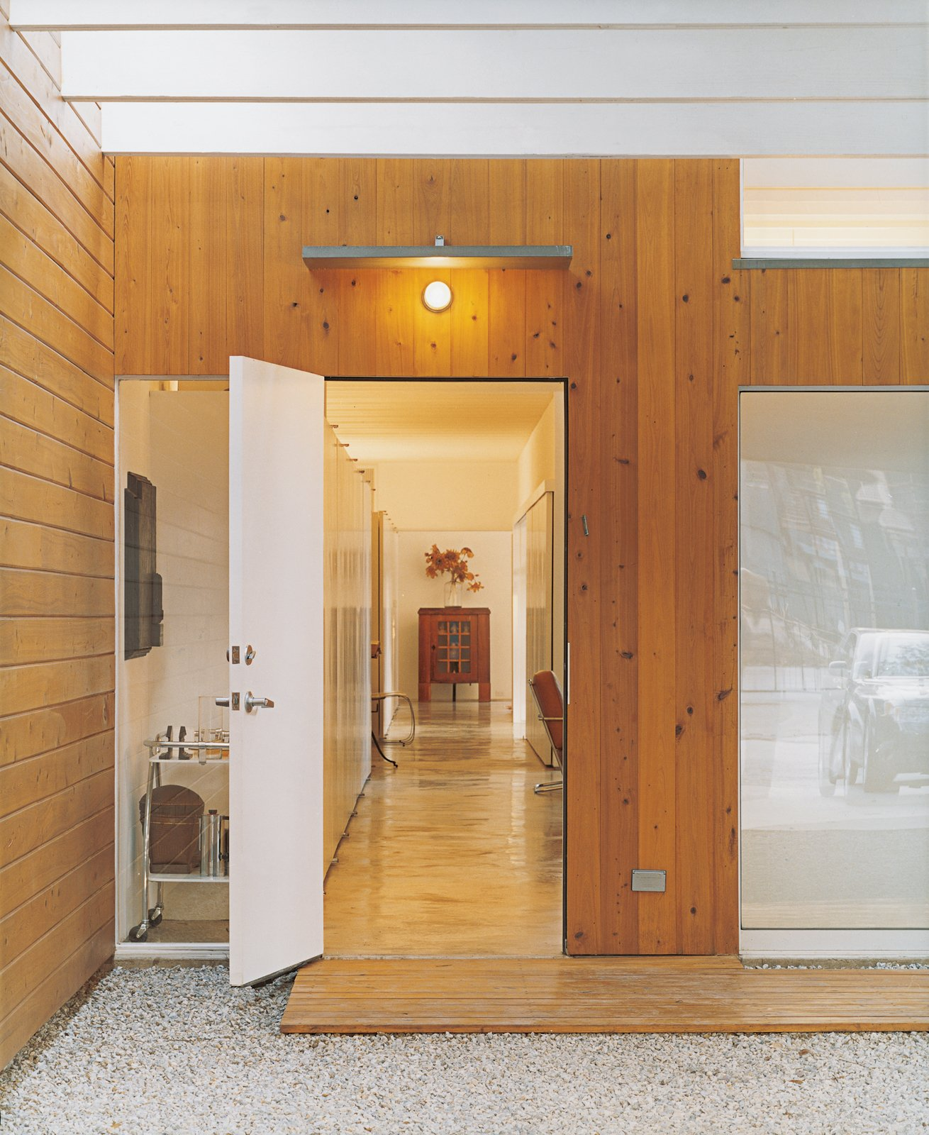 The backlighting Baum included above the storage units lining the hall is revealed at dusk. The lighting provides a warm glow throughout the house.  60+ Modern Lighting Solutions by Dwell from Bringing Families Back to Downtown Dallas