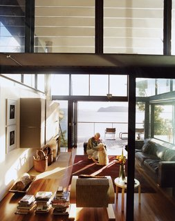 The living room structure soars to two stories, with banks of glass louvers at the upper level providing cross ventilation.