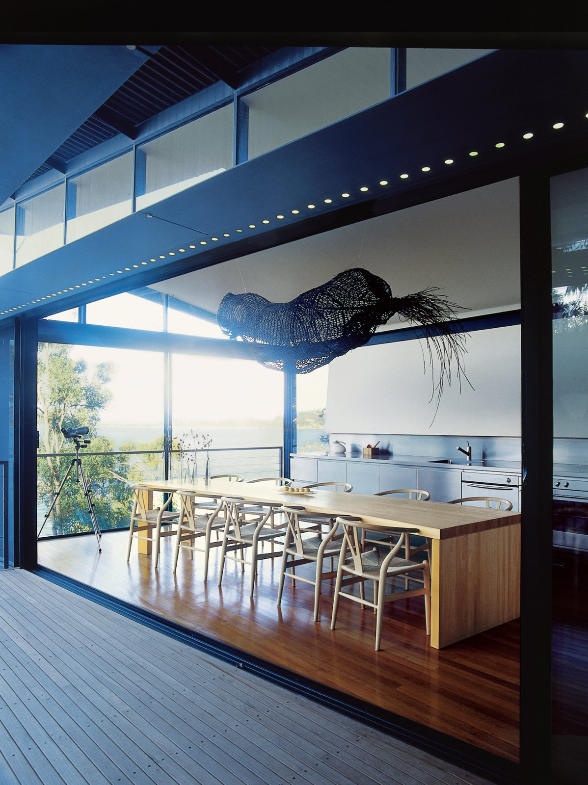 Medium Hardwood Floor, Dining Room, Chair, and Table ૠ  Kitchen from Three Glass-and-Copper Pavilions Conquer the Cliffs