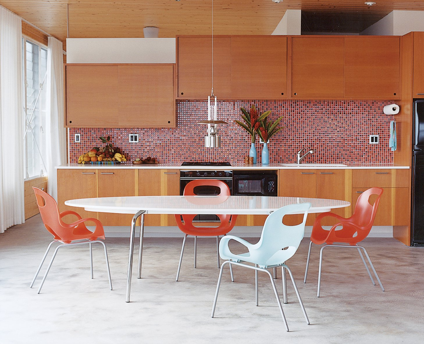 Kitchen, Mosaic Tile Backsplashe, and Wood Cabinet The concrete floor takes on a silky appearance in the kitchen and dining areas. The Gideå table is from IKEA, the Karim Rashid Oh chairs are from Umbra, and the Erik Magnussen kerosene Ship's lamp is by Stelton.  Photo 9 of 11 in Go With the Flow