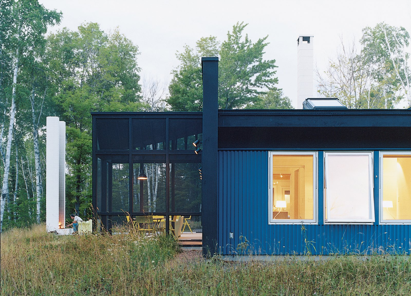 "Exterior, Metal Siding Material, House Building Type, Glass Siding Material, Metal Roof Material, and Flat RoofLine A side view of the house and of Salmela's signature architectural feature: the ""unchimney."" All windows are from Loewen.  Photos from Off the Beaten Path"