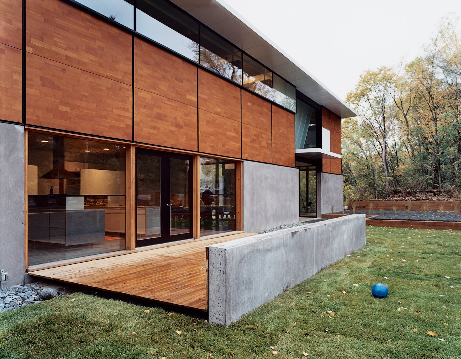 "Exterior, House Building Type, Flat RoofLine, Wood Siding Material, and Concrete Siding Material Front view of the FlatPak House in Minneapolis, Minnesota. When the architect first told his wife about his idea, she said, ""It's about time you focus on a house for me!"" He continues, ""It's like the old story about the cobbler whose kids have no shoes.""  Best Photos"