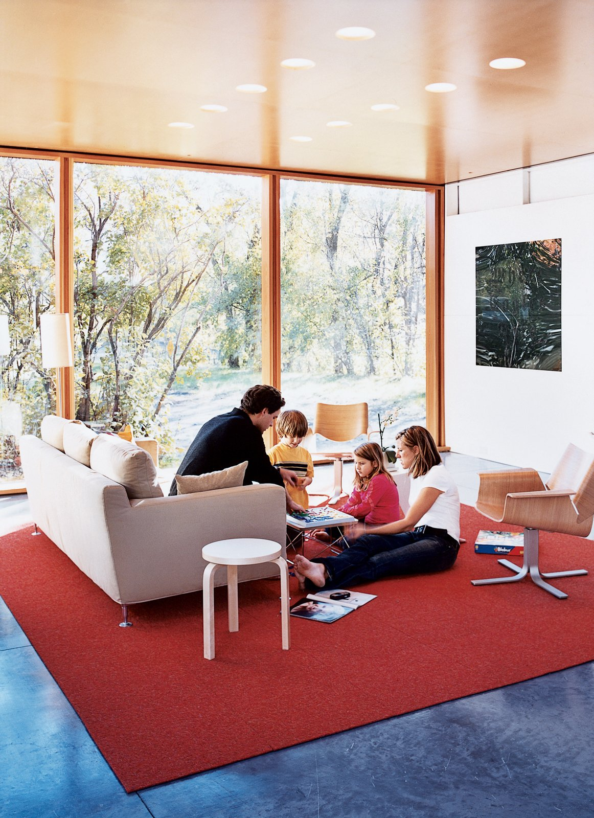 """Living Room, Sofa, Chair, and Recessed Lighting Having lived, he says, in """"a number of houses where the living room is the most adorned and the least used,"""" it was important for Lazor to create a functional family living space. As the gathering above attests, it worked. The carpet is by InterfaceFLOR, and the armchairs by Blu Dot.  Photos from How to Play FlatPak"""