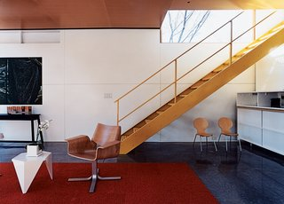 The industrial stair leads to the upper level, where the bedrooms, bathrooms, and play space are located.