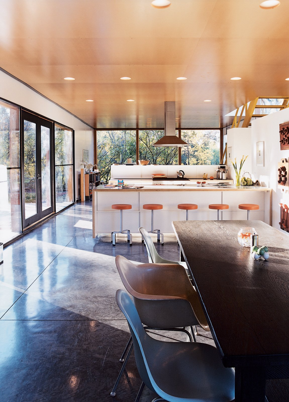 """Kitchen, Range Hood, and Wood Counter """"It was a major decision to put the kitchen in the center where everything would revolve around it,"""" says Lazor. """"We did this simply by following what patterns we observed—it was just where people gravitated."""" The bar stools are by Blu Dot, and the chairs by Charles and Ray Eames.  Photo 4 of 10 in How to Play FlatPak"""