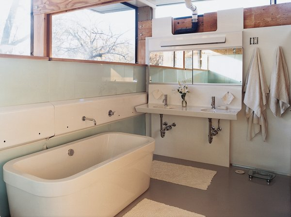 The master bath contains all functions in the white fiberglass panel that runs the length of the wall. Lazor designed the vanity; the tub is by Duravit.