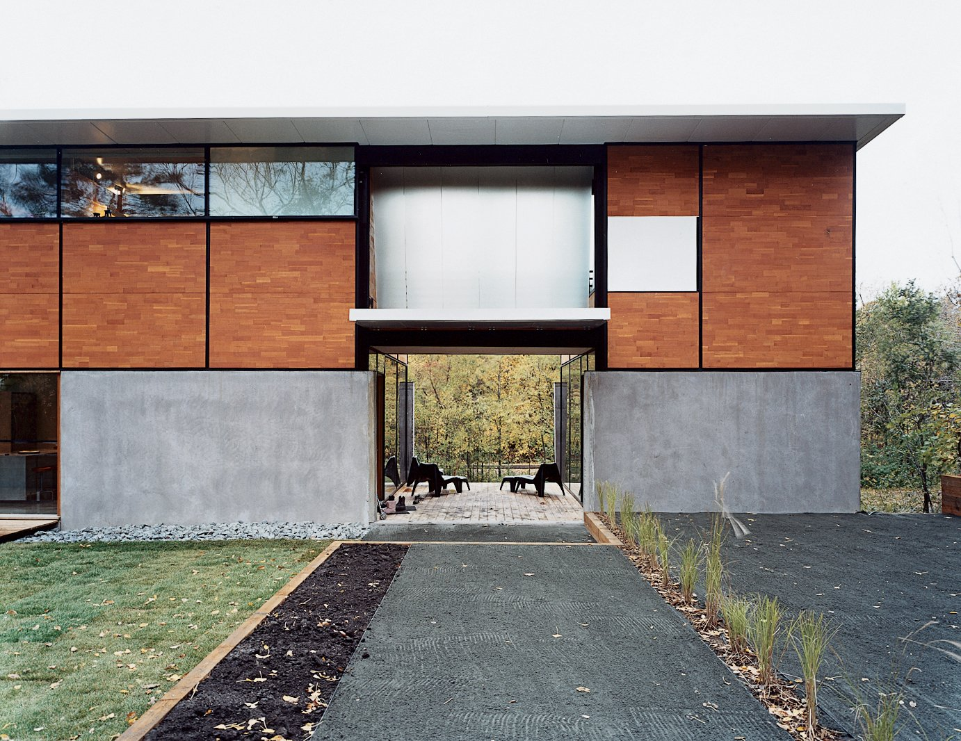 "Exterior, House Building Type, Wood Siding Material, Concrete Siding Material, and Flat RoofLine The courtyard is just one of many open spaces that will be highly utilized—in the non-winter months anyway. Concrete worked well with developing the language of FlatPak. The second level is a wood panel that can be clad in corrugated metal or cedar—different layers that can be plugged in like covers on your cellphone.  Search ""modern home young hollywood"" from How to Play FlatPak"
