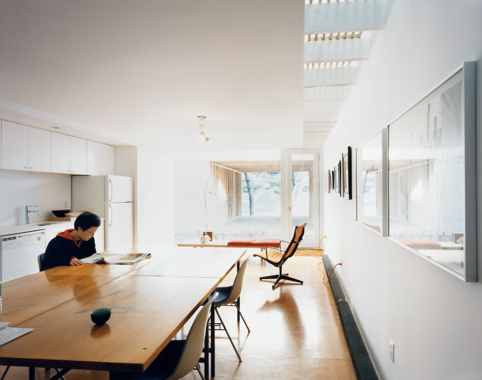 Kim reads the newspaper in the all-white kitchen. White paint, which requires fewer coats than color, was a money-saving strategy. The desk chairs and aluminum lounge chair are both Eames, courtesy of Fernandez's scavenging.  Photo 7 of 11 in New Beginnings