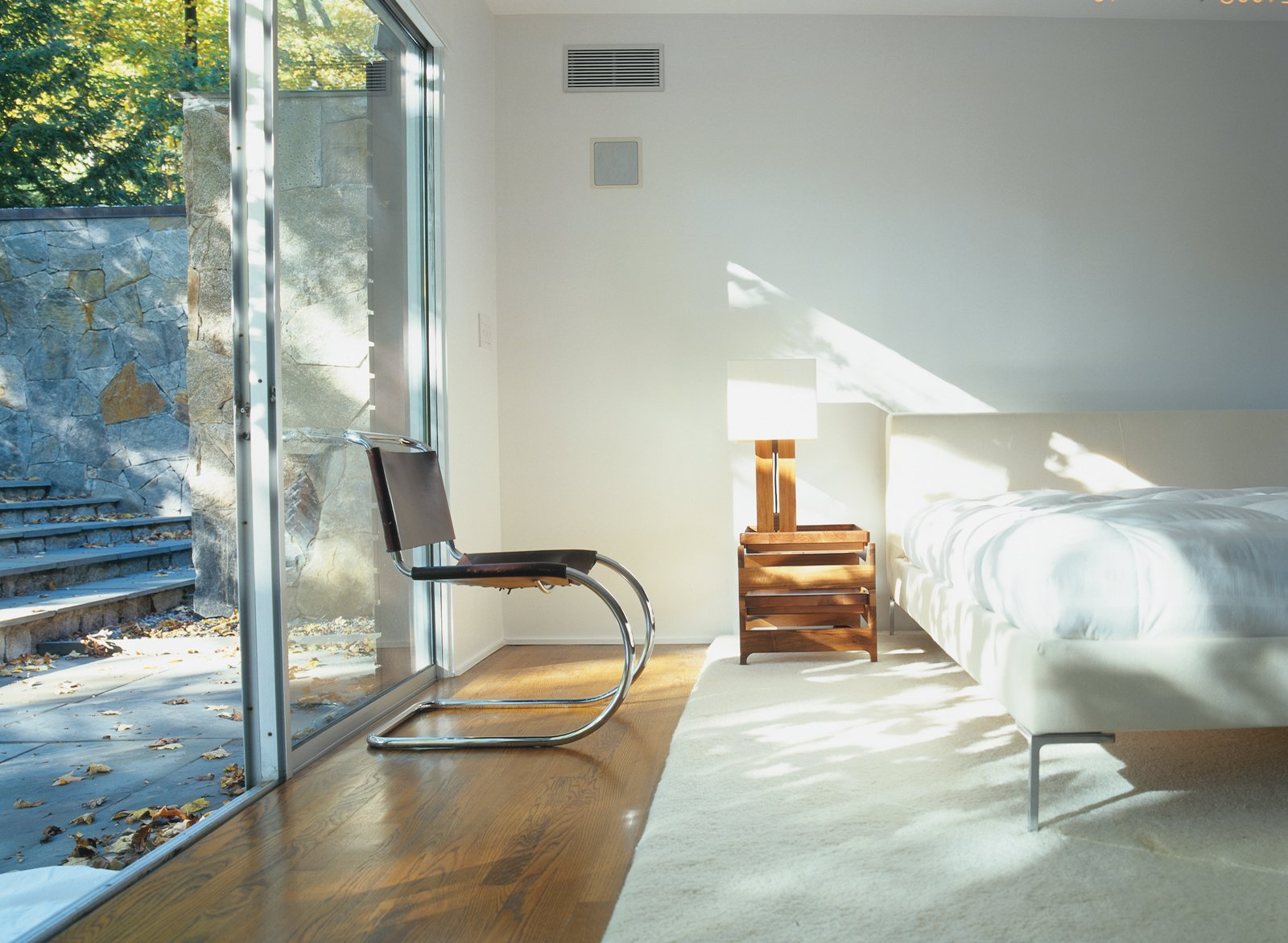 Bedroom, Bed, Chair, and Medium Hardwood Floor The master suite was fashioned from the house's original garage in a 1970s renovation.  Best Photos from Pursuing Perfection
